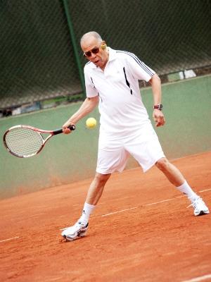 Foto de un hombre de tercera edad jugando tenis