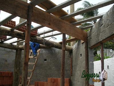 Execução da laje em cima da viga de madeira de eucalipto tratado com os pilares de madeira na alvenaria de bloco de cimento.