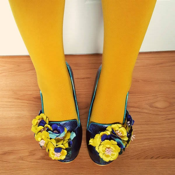 close up detail of flowers on blue shoes worn with mustard tights