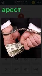 Руки за спиной в наручниках с деньгами в руках,арест чиновника