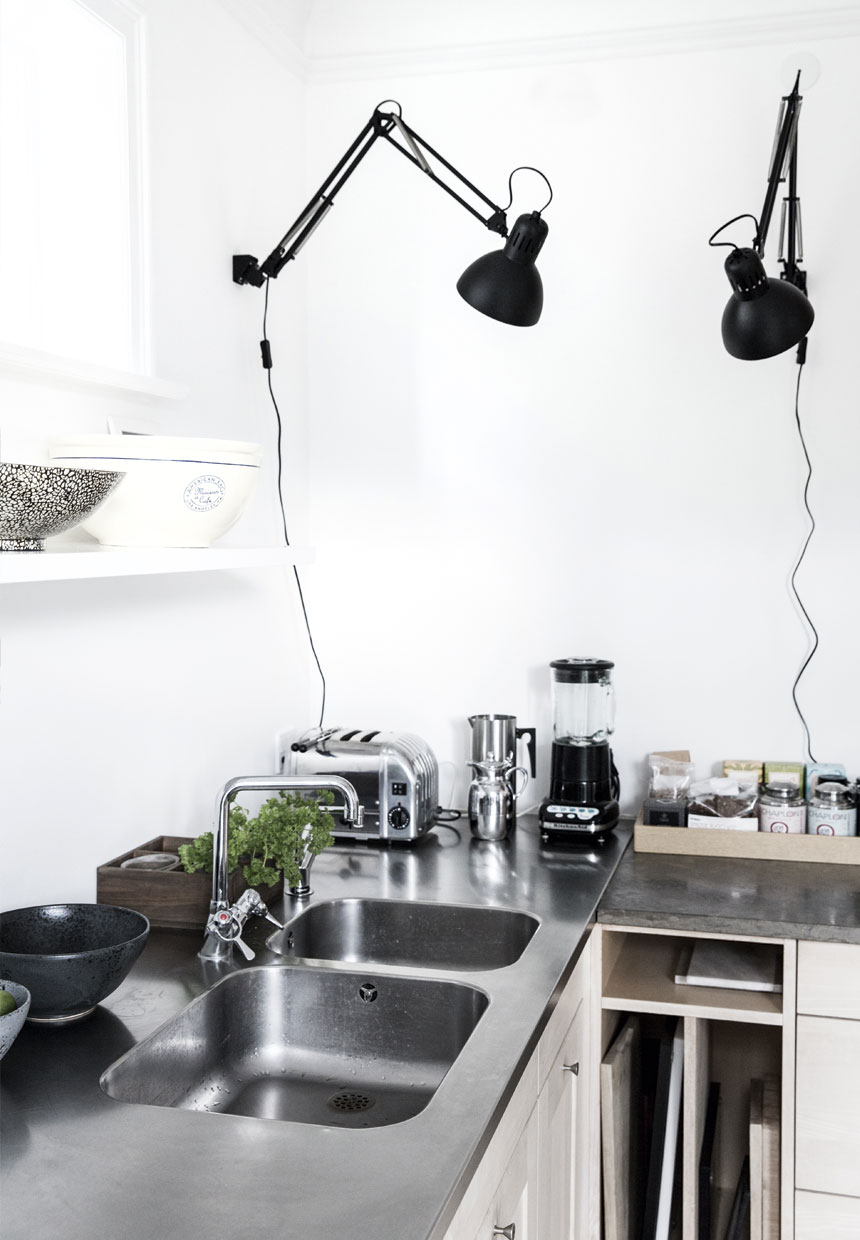 White kitchen inside of Scandinavian villa, black decor, stainless desk