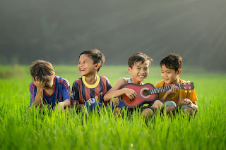 God smiles when I trust Him.  Boys smiling and playing small guitar in field
