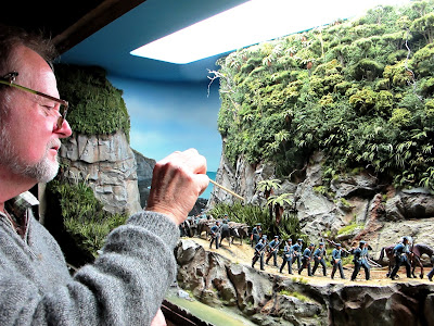 Man pointing a stick at miniature cabbage trees  in a diorama.