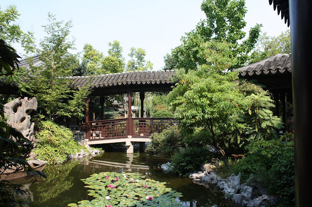Footbridge through calming scenery with lily pads about at Lan Su Chinese Garden.