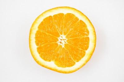 Imagen de una naranja partida por la mitad tras un fondo blanco (plano picado)