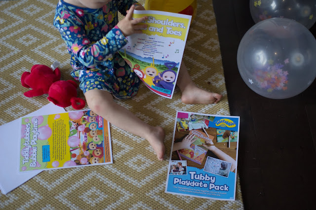 A toddler surrounded by party decorations and printed pages of the Tubby Playdate Pack