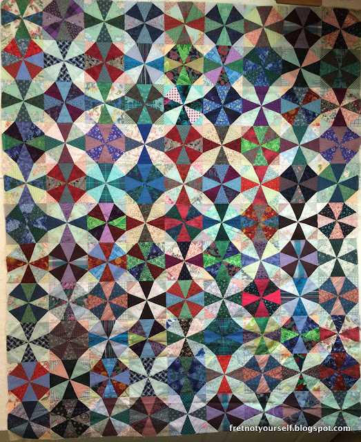Deep red, purple, blue, and blue-green fabrics sorted by value highlight the circles of the kaleidoscope quilt pattern.