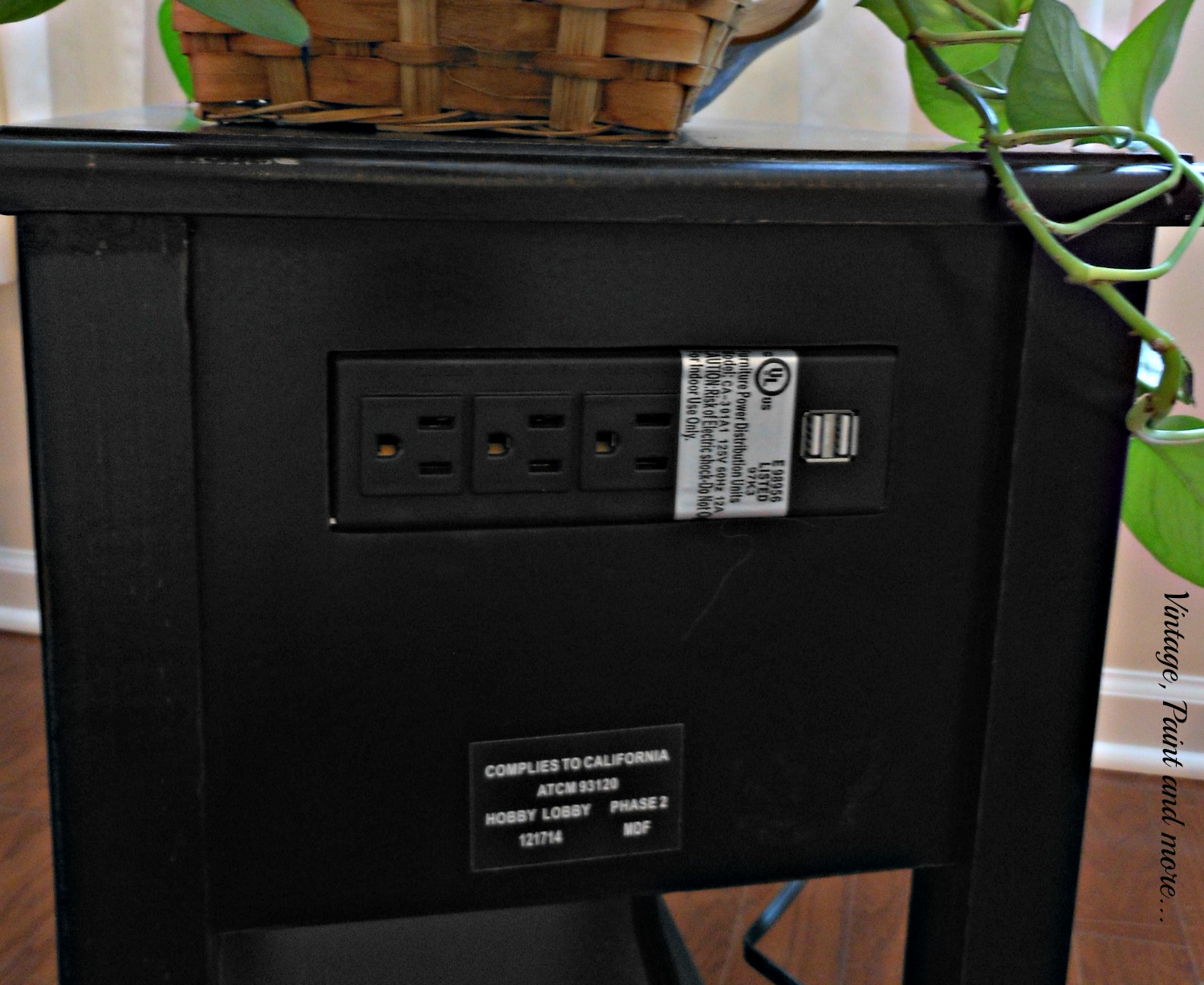 a small side table with electrical outlets and USB ports to charge your eclectronics