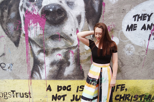 Lyd stands in front of a dalmation wall mural, wearing a black top and multicolour trousers