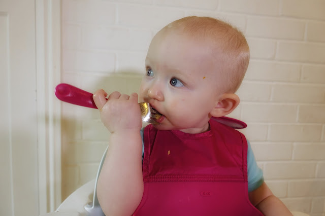 A baby with blue eyes stares wistfully into space with a fork in her mouth