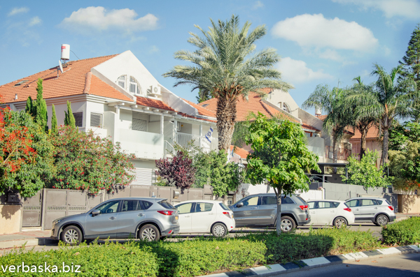 Typical white two-floor townhomes with a red tiled roof with a penthouse in the living neighborhood in Israel