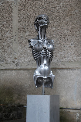 A metallic bust sculpture of an alien woman.