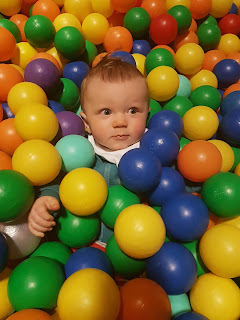 baby in ball pit surrounded by colourful balls