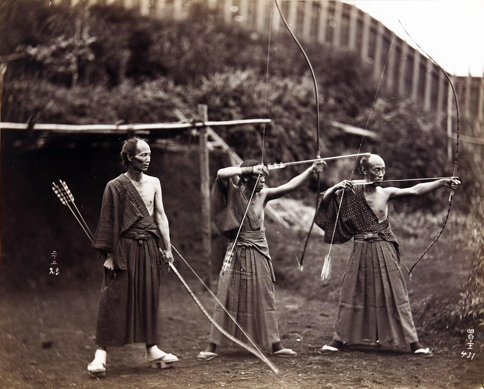 Three archers stand poised in an outdoor setting, 1860 - ca. 1900.