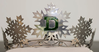 "A tiara topped with silver snowflakes and a green ""D."""