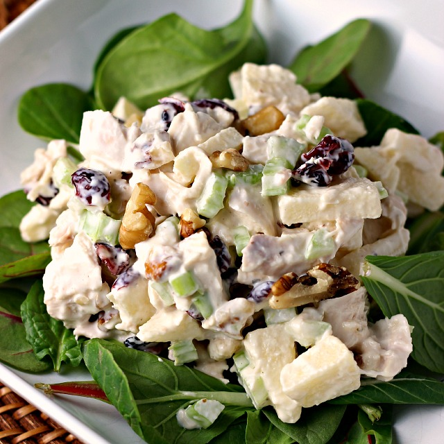 Waldorf Style Chicken Salad on white plate with spinach