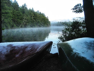 Two canoes on the shore of a foggy lake