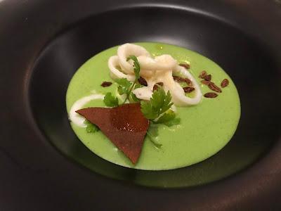 Sort bolle med grønn suppe med blekksprutringer og noen blader på toppen.