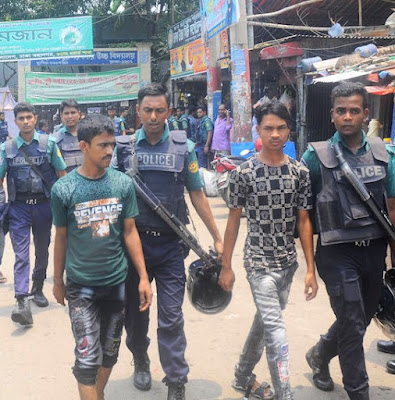 Police detain suspected drug dealers during a raid in Dhaka on June 20.