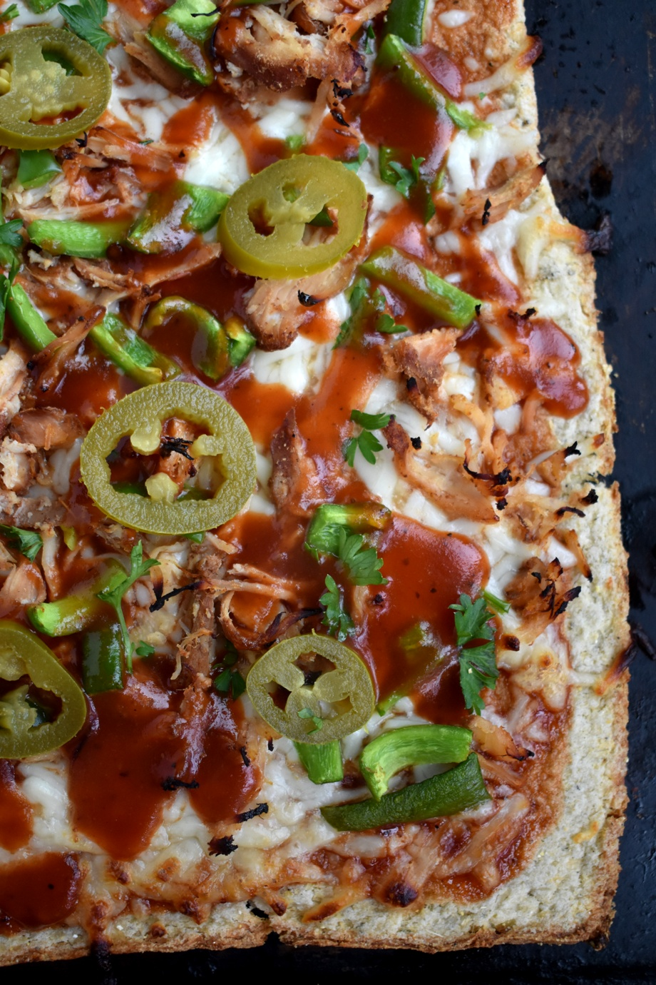 BBQ Chicken Pizza with Cauliflower Crust is nutritious with an 80% cauliflower crust and is topped with shredded chicken, BBQ sauce, mozzarella cheese, bell peppers and jalapenos! www.nutritionistreviews.com #pizza #bbq #cauliflower #healthier #dinner