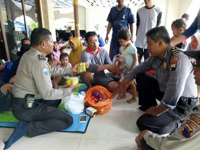 Polisi Berikan Jajanan Kepada Anak-anak Korban Banjir