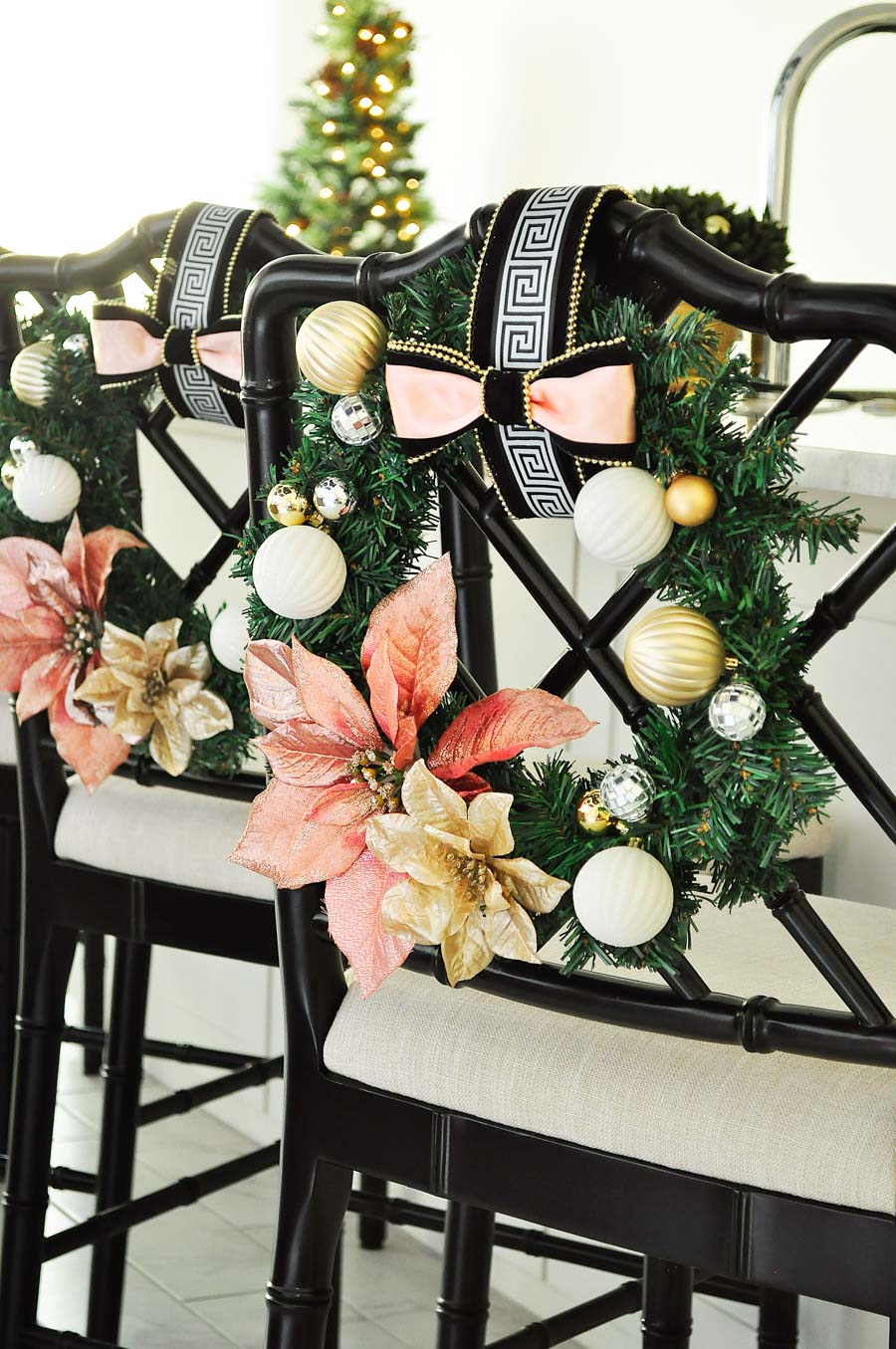 A gorgeous and glam blush, white, and gold chair wreath perfect for holiday and Christmas decor in a kitchen or dining room. Love the Greek Key accents! An easy DIY project.