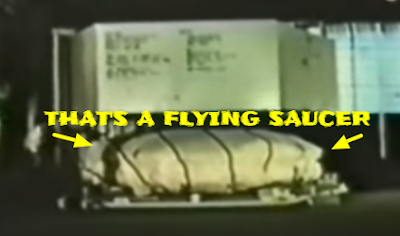 Flying Saucer under a cover been transported in a box.