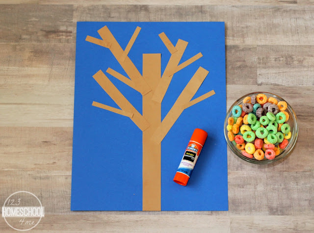 glue brown rectangle pieces onto blue construction paper to make fall tree
