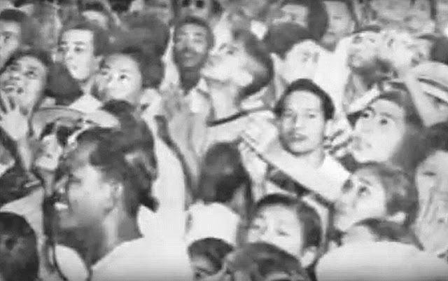 People in the crowd had their eyes aimed at the sky hoping for petal showers.  Image captured from June Keithley and Center for Peace Asia documentary on YouTube.