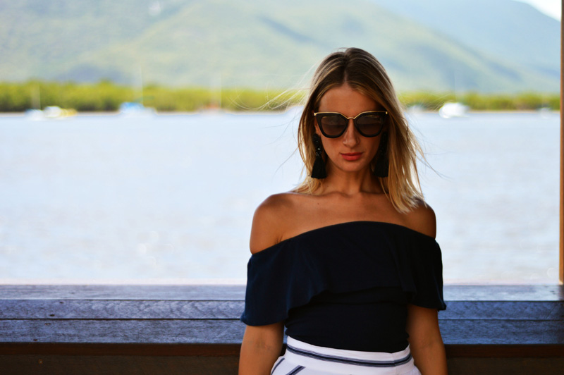 street style girl in front of sea wearing prada cinema sunglasses and navy off shoulder top with blonde balayage lob