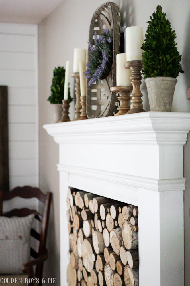 DIY faux fireplace with stacked wood in farmhouse style dining room