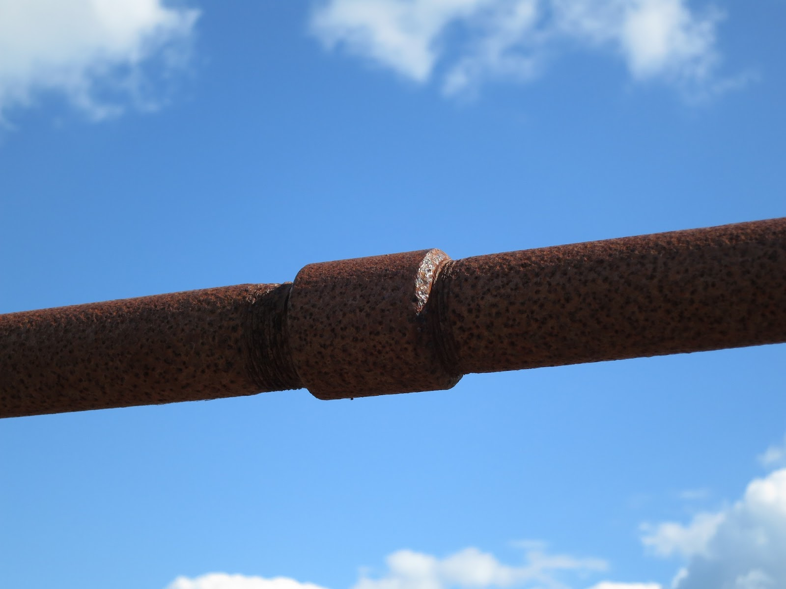 Rusty rail of bridge against blue sky with puffy white clouds.