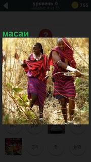 В тростнике идут масаи женщина и мужчина в национальных одеждах