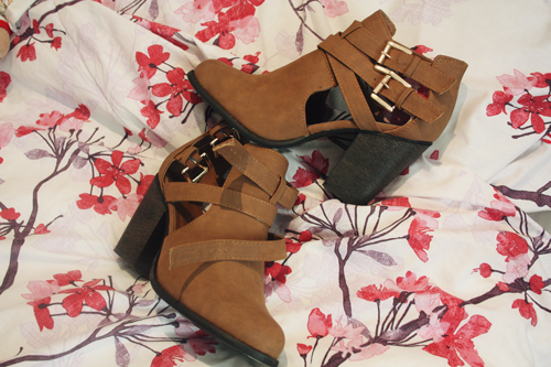 tan cut out ankle boots with slight heels and two gold buckles on overlapping straps on the side, sitting next to each other on a red and pink floral bedspread on francescasophia.co.uk