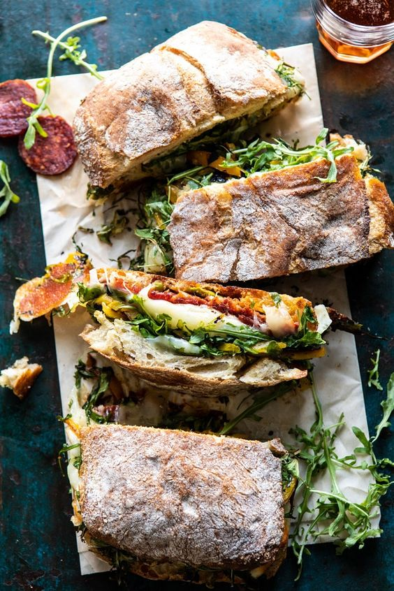 Crusty ciabatta bread, sandwiched with homemade Italian vinaigrette, spicy salami, salty prosciutto, fresh baby arugula, roasted peppers, provolone AND mozzarella. It's the easiest way to serve up a melty sandwich to a hungry group of guests. Perfect for your game day eats!