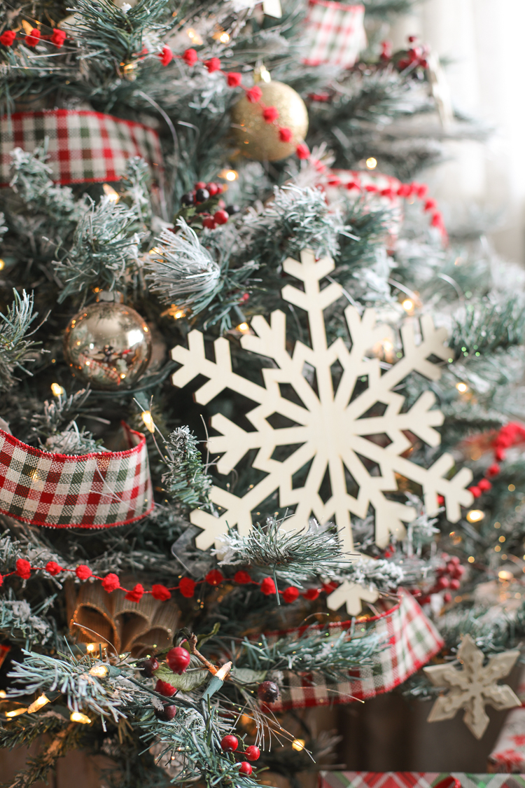 Oversized wooden snowflakes, plaid ribbon and pom pom trim on a Christmas tree