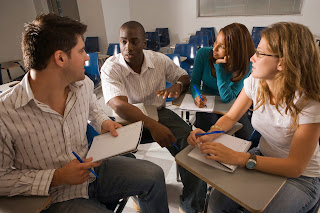 A group of male and female students interact in a classroom setting.