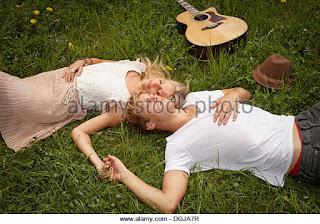 Νεαρό ζευγάρι ξαπλωμένο στο γρασίδι.