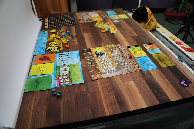 A table with the Bee Lives board game spread out on it.
