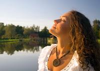 Doğada temiz havada gözleri kapalı nefes alan bir bayan