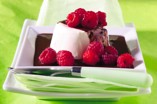 panna cotta in a pool of chocolate and fresh raspberries