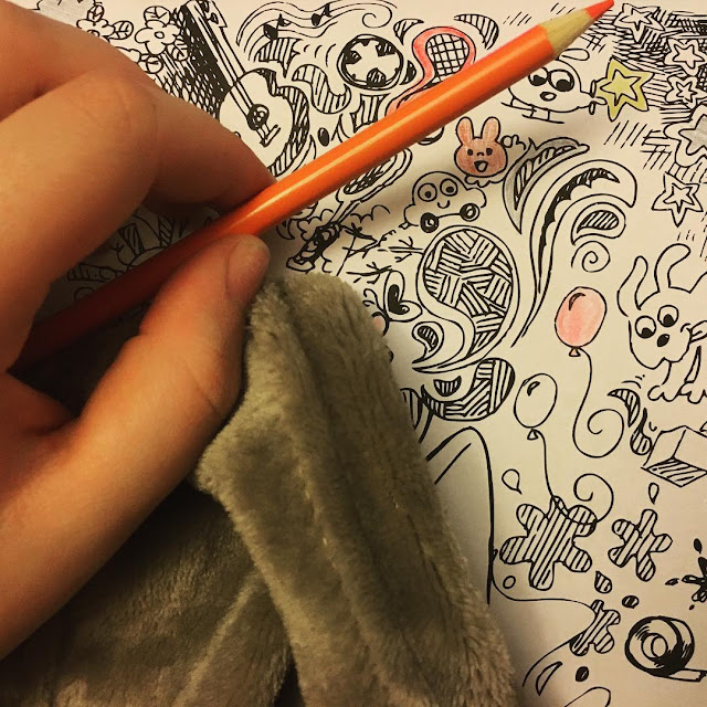 Photo of an adult colouring book, orange pencil, and cosy blanket in a list of ways to cope when you're not coping
