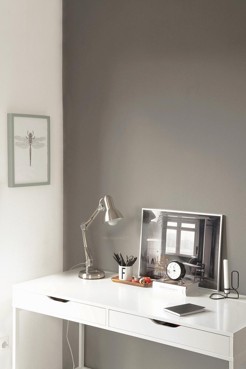 Weißer Schreibtisch vor grauer Wand, moderner reduzierter Arbeitsplatz. Dekorieren in monochromen Farben.