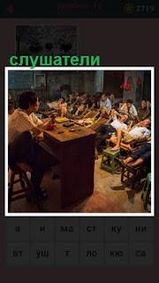учитель за столом и перед ним слушатели сидят