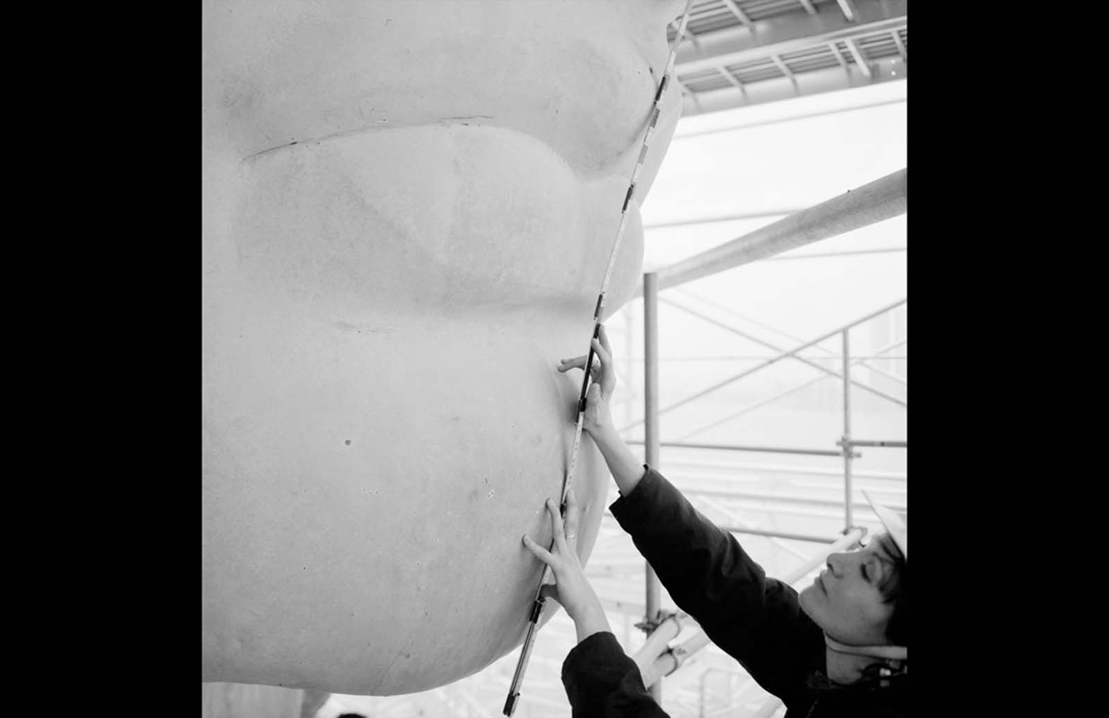 A nose and mouth detail with a worker named Isabel Hill holding a scale stick, during restoration work in March 1985.