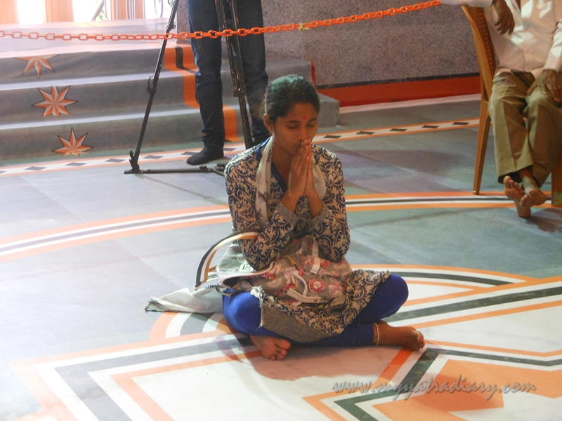 A girl in prayer at Andhericha Raja life size Ganesha pandal, Mumbai