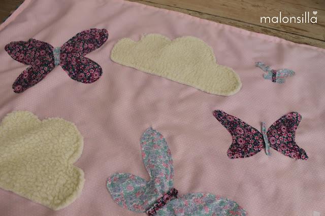 Detalle de la manta con nubes de borreguito y mariposas de diferentes colores by malonsilla