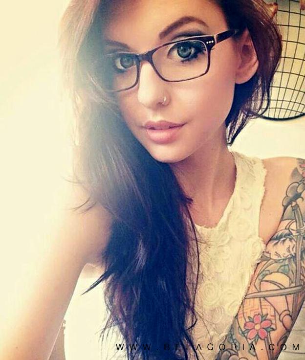fotografia de una joven con gafas posando con tatuajes en el brazo