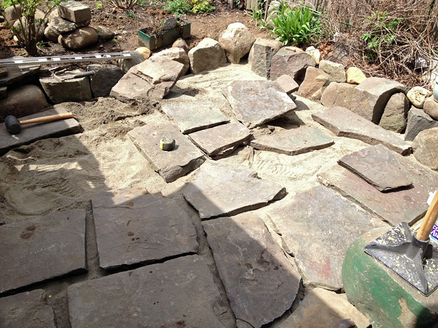 Reclaimed slate backyard patio Artist and Builder laying out slate for proper fitment