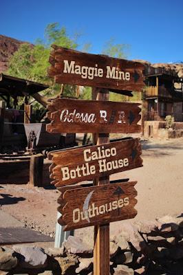 Uma placa estilizada de Velho Oeste em Calico Ghost Town, indicando os lugares que podem ser visitados na cidade.